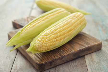 sweetcorn: Raw corn cobs on wooden background closeup Stock Photo