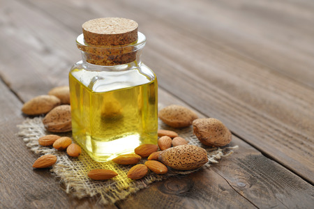 Almond oil in bottle on wooden background photo
