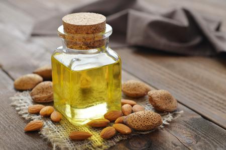 L'huile d'amande dans une bouteille sur fond de bois