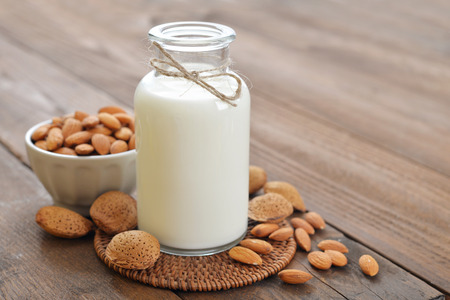 Almond milk in bottle with nuts on wooden background Imagens