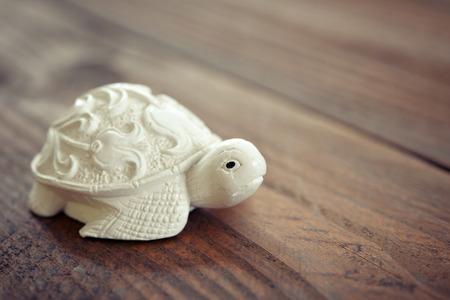 Ceramic figurine of turtle on wooden background photo