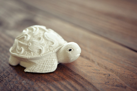 ancient turtles: Ceramic figurine of turtle on wooden background