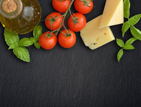 dark grey slate: Ingredients of italian cuisine  - cherry tomato, basil, parmesan and olive oil - on dark background
