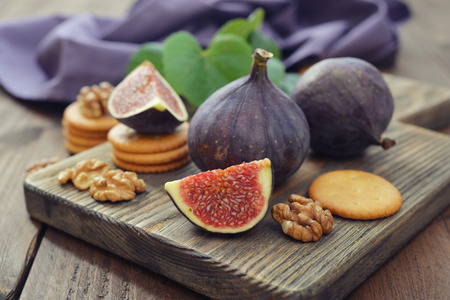 Fresh figs with walnuts and crackers on wooden background