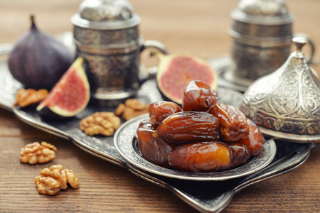 Cup of coffee with dry dates on metal oriental tray