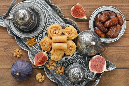 comida arabe: Taza de café con baklava y metal bandeja oriental sobre fondo de madera