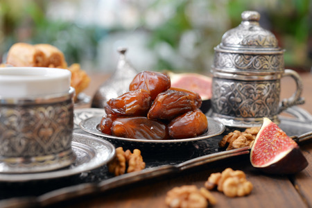 Dry dates with cups of coffee on metal oriental tray