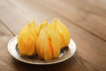 cape gooseberry: Physalis fruits on plate closeup on wooden background Stock Photo