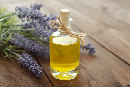 Essential lavender oil with fresh flowers on wooden background closeup