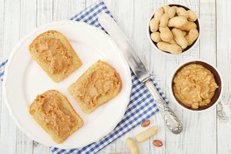 allergic ingredients: Peanut butter sandwich on plate with nuts on wooden background. Top view