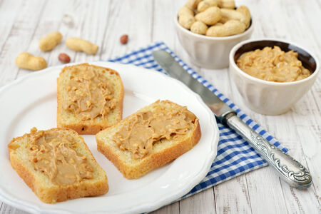 allergic ingredients: Peanut butter sandwich on plate with nuts on wooden background