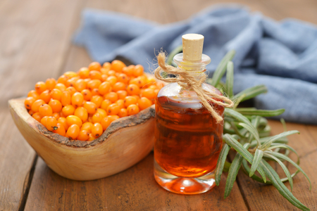 officinal: Sea-buckthorn oil and berries in bowl on a wooden background Stock Photo