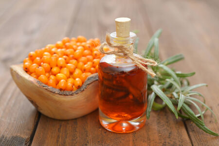 buckthorn: Sea-buckthorn oil and berries in bowl on a wooden background Stock Photo