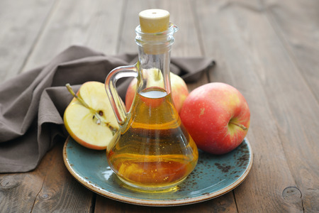 Apple cider vinegar in glass bottle and  fresh apples on wooden background