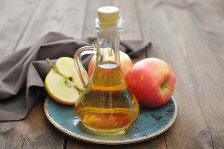 acido: El vinagre de manzana en botella de vidrio y manzanas frescas sobre fondo de madera