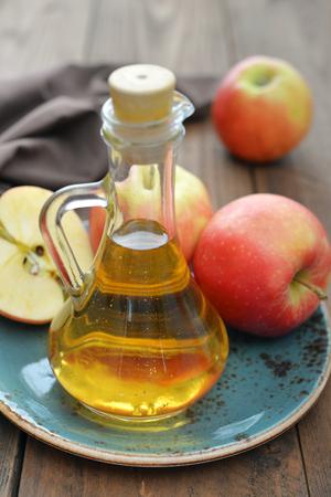vinegar bottle: Apple cider vinegar in glass bottle and  fresh apples on wooden background