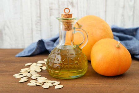 pumpkin seeds: Pumpkin seed oil in bottle with seeds and pumpkin on wooden background