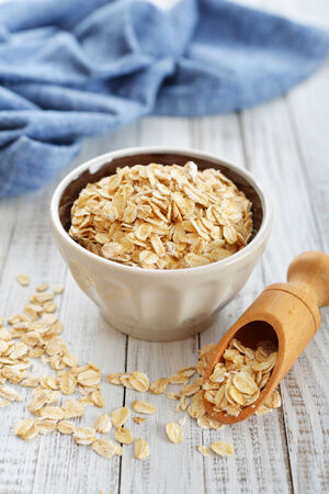 Oat flakes in bowl on white wooden background photo