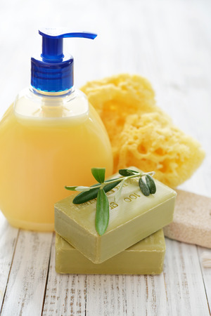 Shower gel with olive soap and bath sponge on wooden background photo