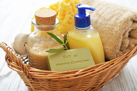 Shower gel with olive soap and bath towels in basket on wooden background photo