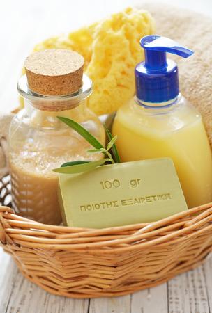 gel douche: gel de douche avec savon de bain et serviettes oliviers dans le panier sur fond de bois
