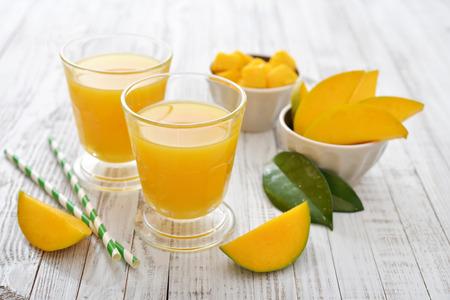 mango: Sok z Mango w szklance na białym tle drewnianych