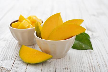 Rebanadas frescas maduras del mango en tazón en fondo blanco de madera Foto de archivo - 32760934
