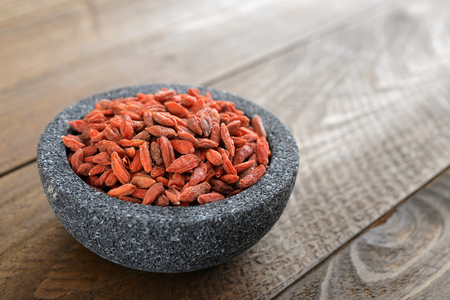 Bowl with goji berries on the table closeup photo