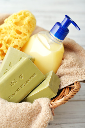 translates: Greek olive soap with bath towels and bath sponge in basket closeup. The words on soap translates as best quality
