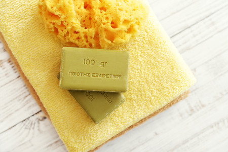 translates: Greek olive soap with bath towels and bath sponge on wooden background. The words on soap translates as best quality Stock Photo