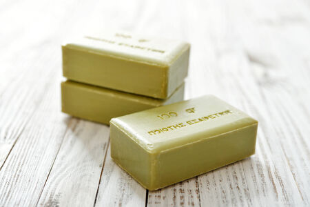 translates: Greek olive soap on wooden background closeup. The words on soap translates as best quality