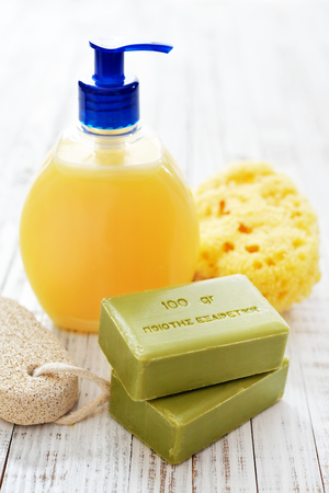 translates: Greek olive soap with shower gel and bath sponge on wooden background. The words on soap translates as best quality Stock Photo