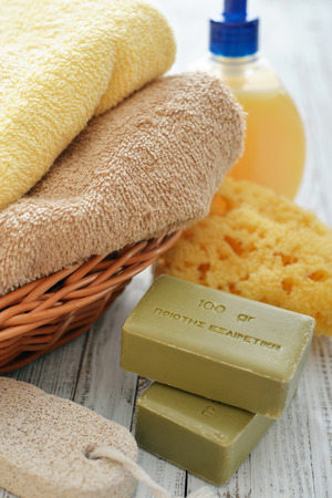 Greek olive soap with shower gel and bath towels on wooden background photo