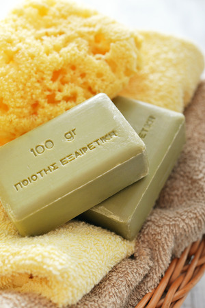 Greek olive soap with bath towels  in basket closeup photo