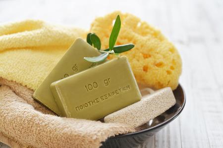 sponge: Greek olive soap with bath towels and bath sponge in bowl closeup
