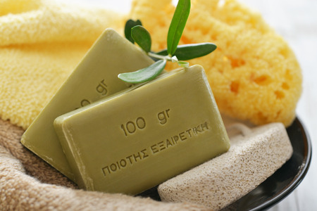 Greek olive soap with bath towels and bath sponge in bowl closeup
