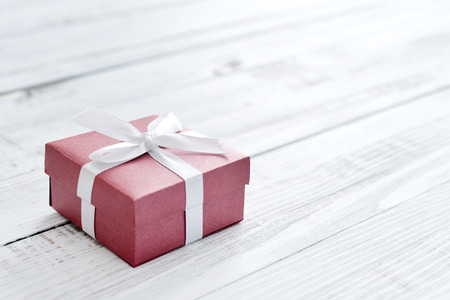 sewing box: Red gift box with white ribbon over white wooden background