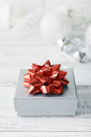 Silver gift box with red bow on wooden background closeup photo