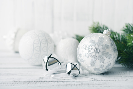 White christmas balls and fir branches with decorations on light background