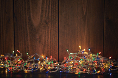 Christmas lights on wooden background. Selective focus Stock Photo