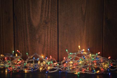 madera r�stica: Las luces de Navidad en el fondo de madera. Enfoque selectivo Foto de archivo
