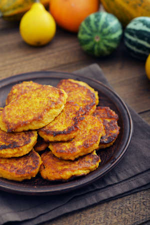 Pumkin pancakes on plate with decorative pumpkin on wooden background photo