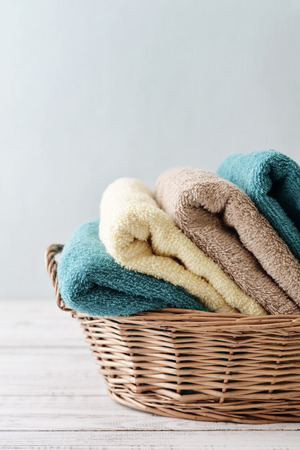 bath: Bath towels of different colors in wicker basket on light background