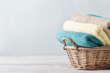 basket: Bath towels of different colors in wicker basket on light background
