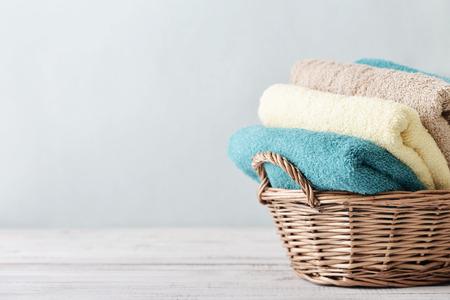 baÑo: Toallas de baño de diferentes colores en la cesta de mimbre sobre fondo claro