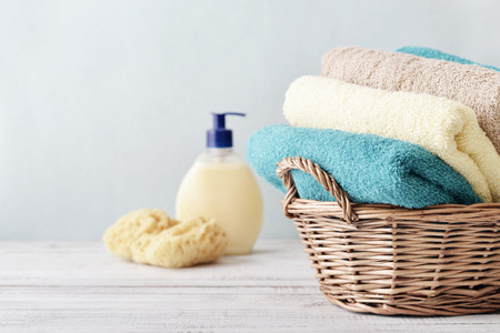 Bath towels of different colors in wicker basket on light background