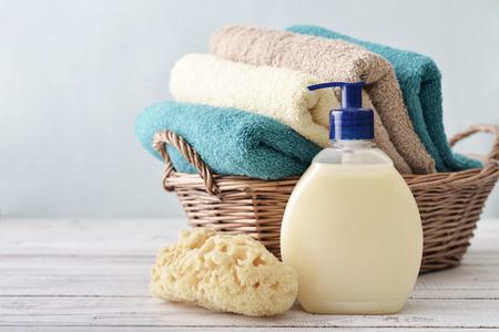 Vloeibare zeep, spons en handdoeken in een rieten mand op een lichte achtergrond