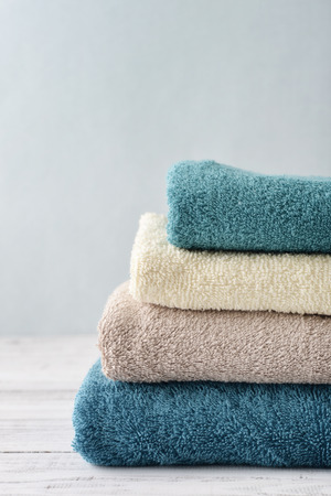 Stack of bath towels on light wooden background closeup Imagens