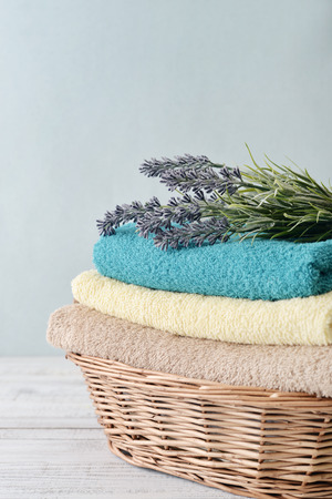 spa still life: Stack of bath towels with lavender flowers in a wicker basket on light wooden background Stock Photo