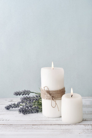 Two candles with lavender flowers on light blue background Stock Photo